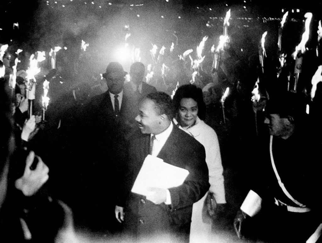 In this Dec. 10, 1964, file photo, through the smoke and fire from hundreds of torches, U.S. civil rights leader and Nobel Peace Prize winner, Dr. Martin Luther King Jr., arrives with his wife Coretta to deliver the traditional Nobel address at the University of Oslo Festival Hall. Behind them is Rev. Ralph Abernathy, King's closest associate. (AP Photo, File) Ref #: PA.21170951
