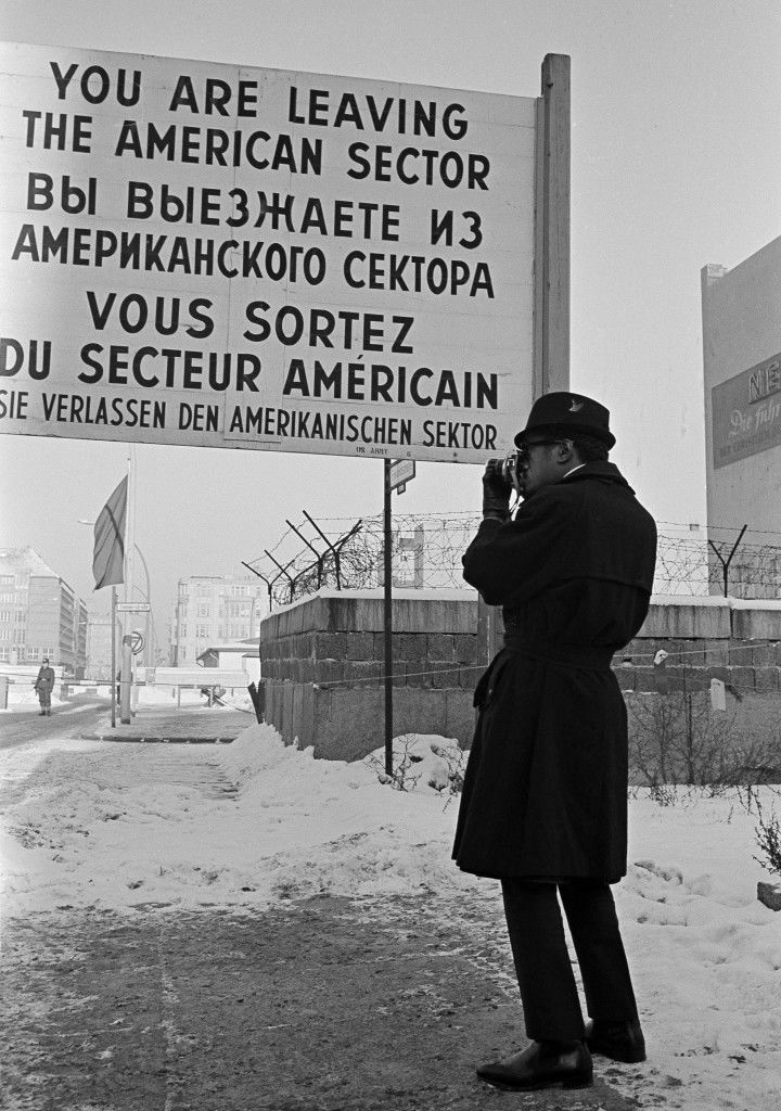 "American entertainer Sammy Davis Jr., takes photographs of the communist built wall as he stands at the borderline of Friedrich Strasse sector border crossing in Berlin, Germany, Jan. 19, 1963. In the background are barriers and part of the wall of the communist checkpoint. Mr. Davis is in Berlin to work on the film remake of ""Three Beggars Opera."" (AP Photo/Edwin Reichert) A-21198496"