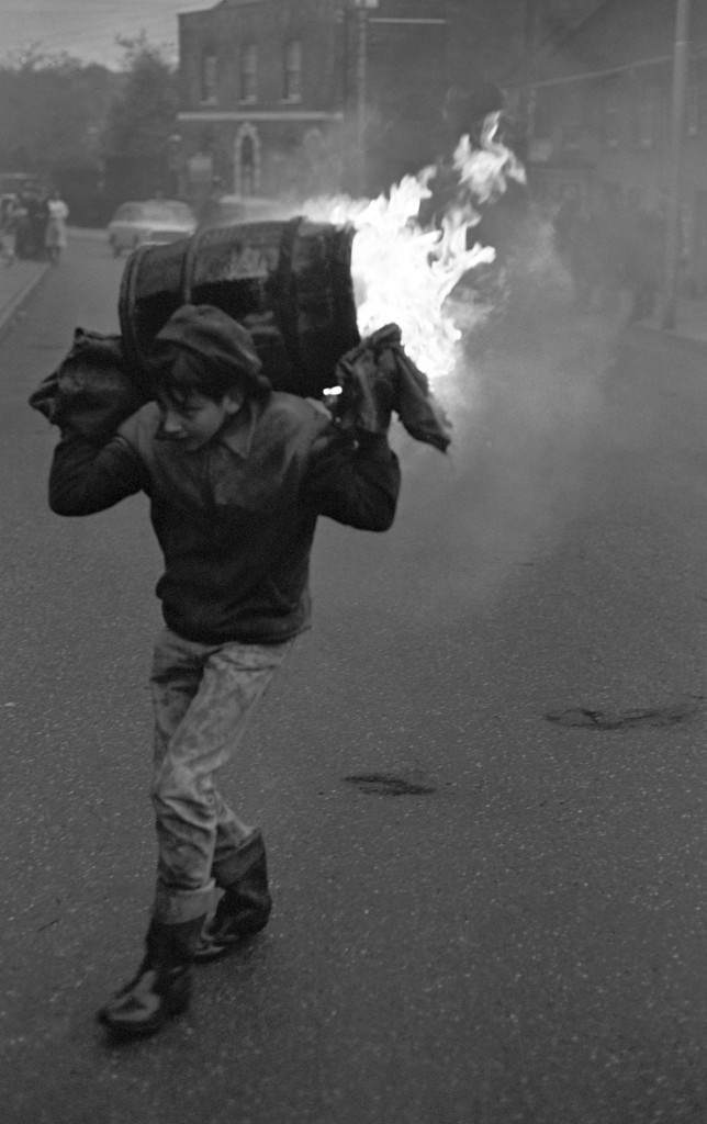 A young boy carries a burning barrel in the street.