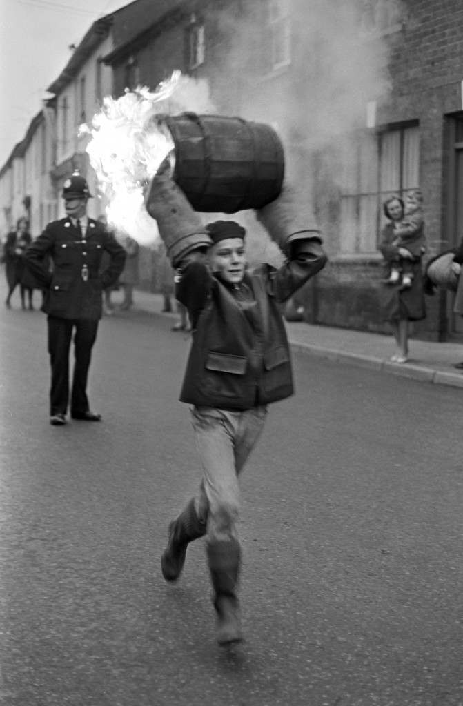 A boy runs through the street carrying a burning barrel during the schoolchildren's event. PA-2278906