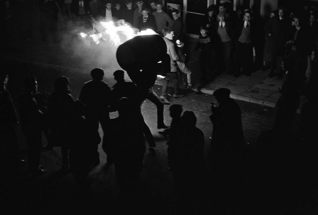 A man runs through the street with a burning barrel as the crowds look on. PA-2278910