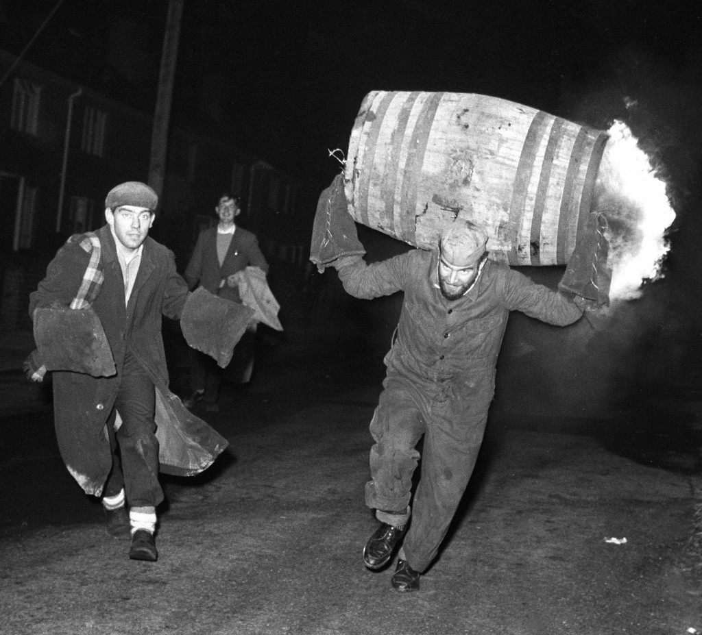 A man runs through the streets carrying a burning barrel on his back.