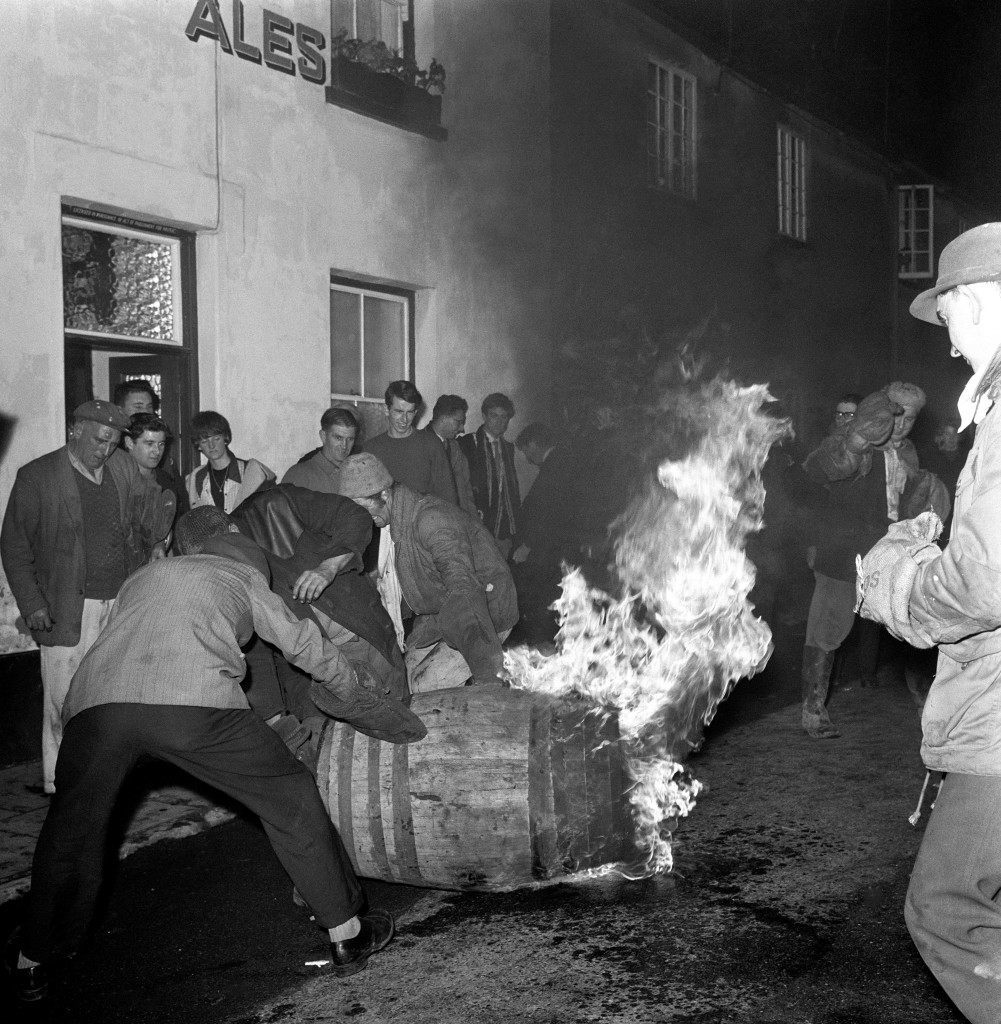 Men in the street outside a pub try to capture a burning barrel.PA-2280265