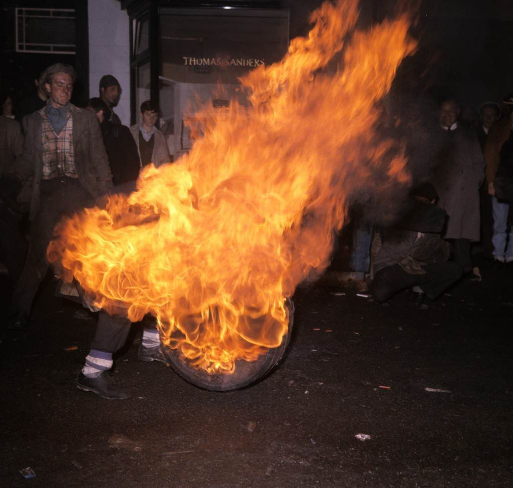 A man tries to get to grips with a burning barrel in the street. PA-2281607.jpg