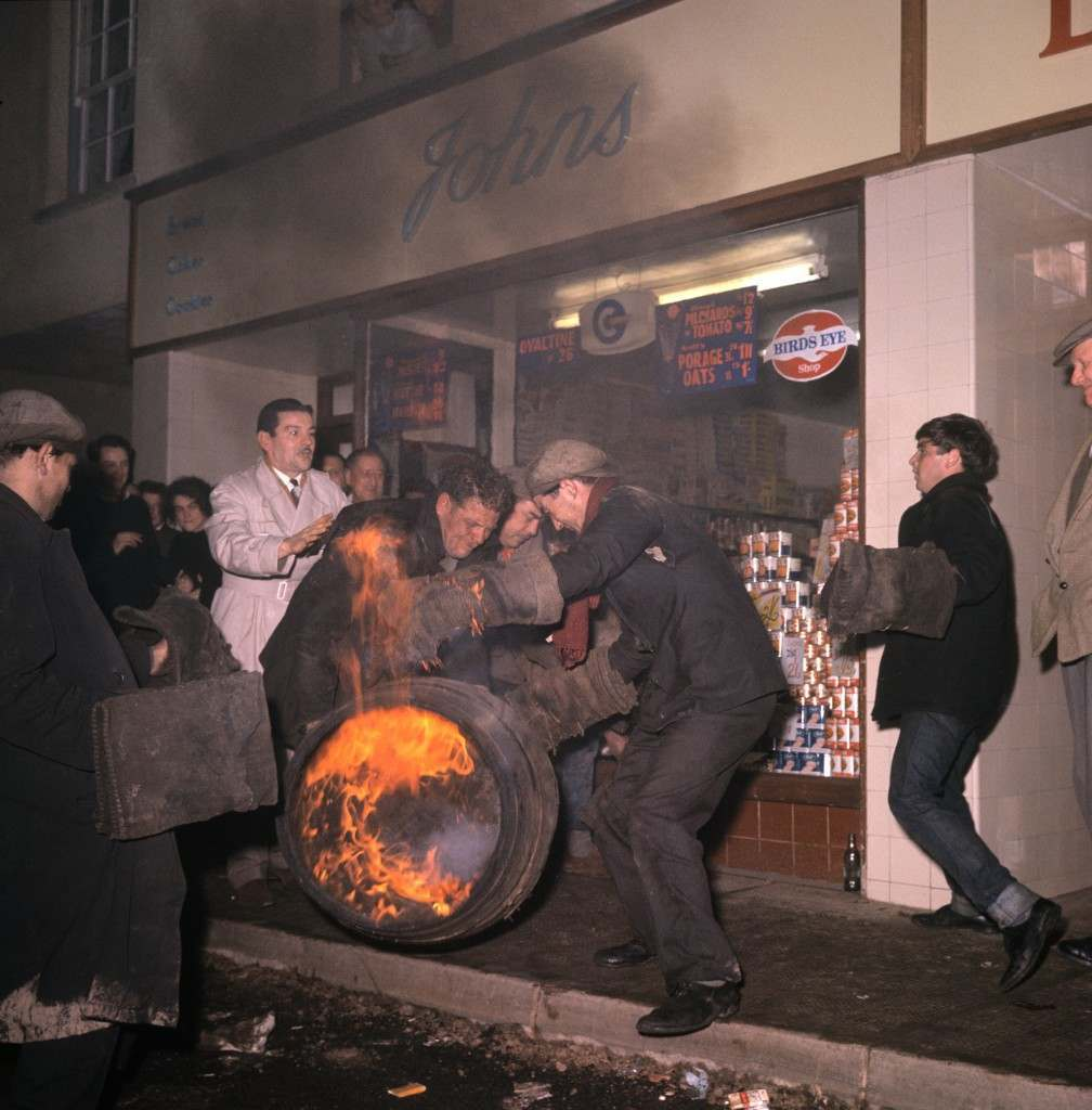 A man tries to get to grips with a burning barrel in the street, as others look on. PA-2281609