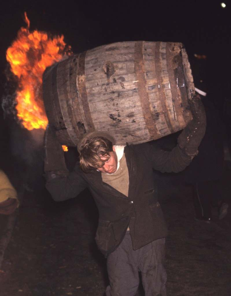 A man runs through the street carrying a burning barrel.