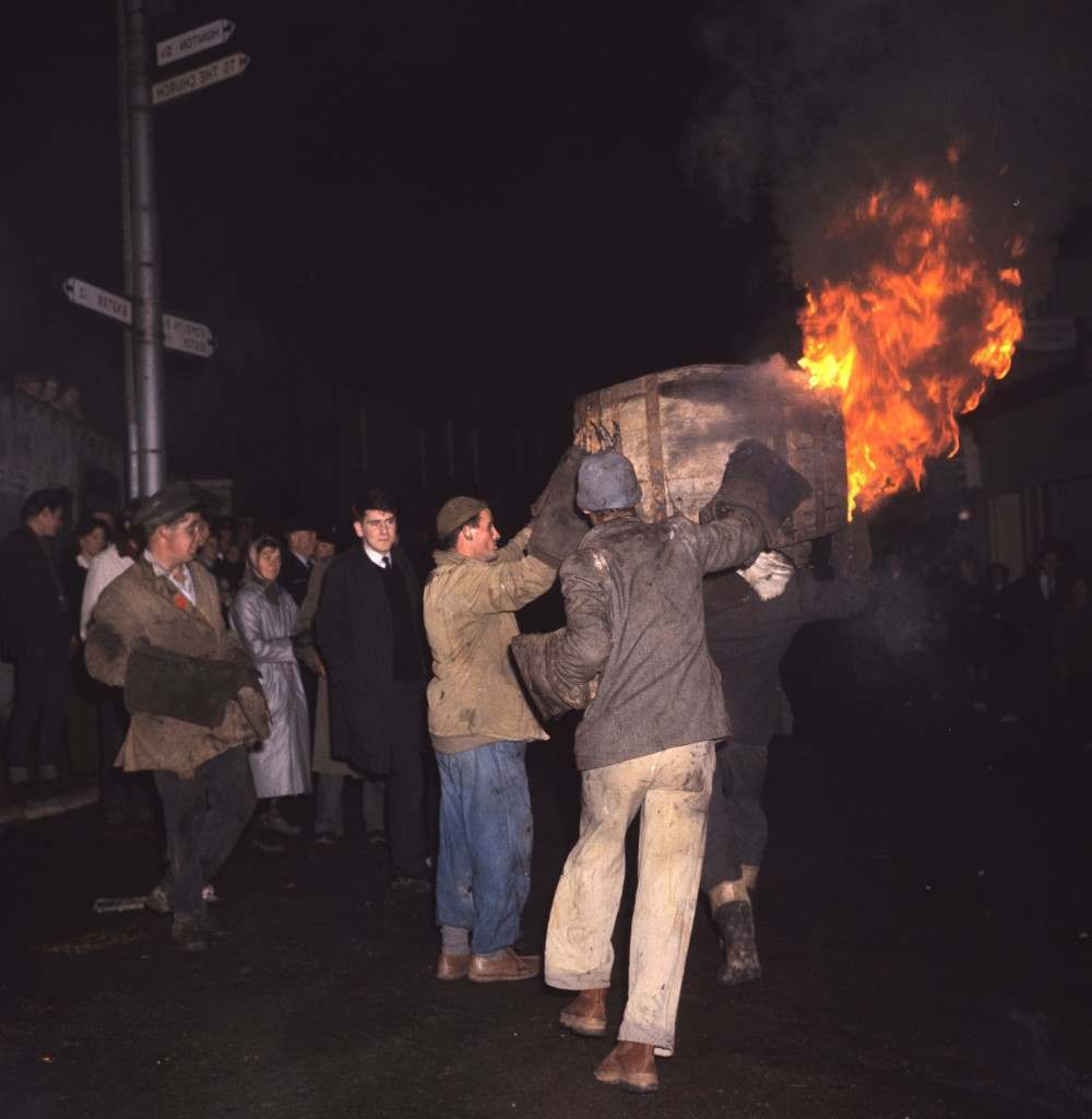 Men carry a burning barrel through the streets as people look on. PA-2288419