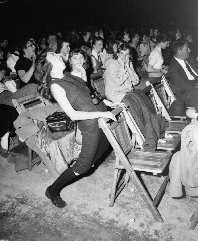 "This unidentified teenager found Elvis Presley ""too much"" when he appeared at the Arena in Philadelphia, April 6, 1957. The girl matched gyrations in her seat with the gyrations of Presley on the stage. Her companion appears a little amazed. (AP Photo) Ref #: PA.2373268  Date: 06/04/1957"