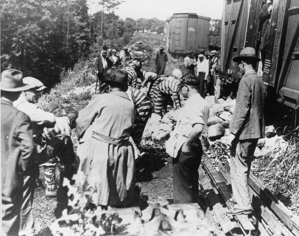 U.S. prohibition agents in Atlanta, Ga., intercept a carload shipment of liquor billed as vegetables from Fort Lauderdale, Fla., to Chicago, Ill., during the alcohol prohibition in this undated photo. Three sqauds of prison inmates, wearing striped prison gear and ankle chains, break up the bottles with sledgehammers. Inside the doors of the train cars, behind a few crates of string beans and potatoes, prohibition agents found crates of pint bottles of whiskey, several thousand in number, piled five deep in the freight car. A telegram from Fort Lauderdale tipped the federal men that the car was coming through Atlanta. Ref #: PA.2470951 Date: 01/01/1933