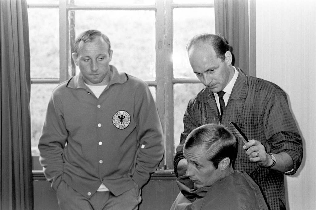 West Germany's Uwe Seeler (l) looks on as teammate Heinz Hornig (r) is given a trim by a local barber at the team's hotel Ref #: PA.2479876 Date: 14/07/1966