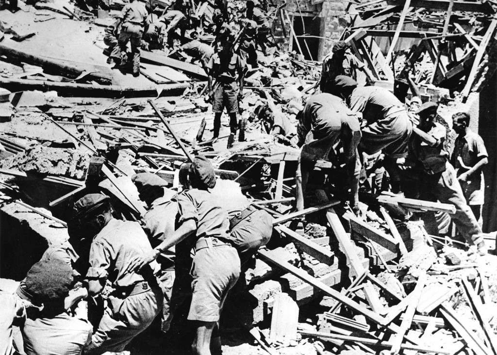 Many lives were lost an dozens of persons were injured when terrorists blew up part of the King David hotel, Jerusalem, which houses the Palestine Government secretariat and the H.Q. of the Palestine Army command. Our Associated press photo shows soldiers digging through rubble of the King David hotel after the explosion on July 22, 1946, to remove dead and injured. Ref #: PA.2508892 Date: 22/07/1946