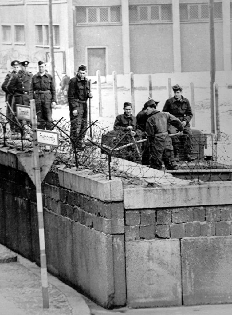 East German soldiers work on a second layer of the Berlin Wall at the allied Checkpoint Charlie crossing near the Friedrichstrasse in the year 1964. East Germany's Communist official built the wall to stop an exodus to West Germany, and it became a symbol of the differences between East and West. (AP Photo) PA-2512704
