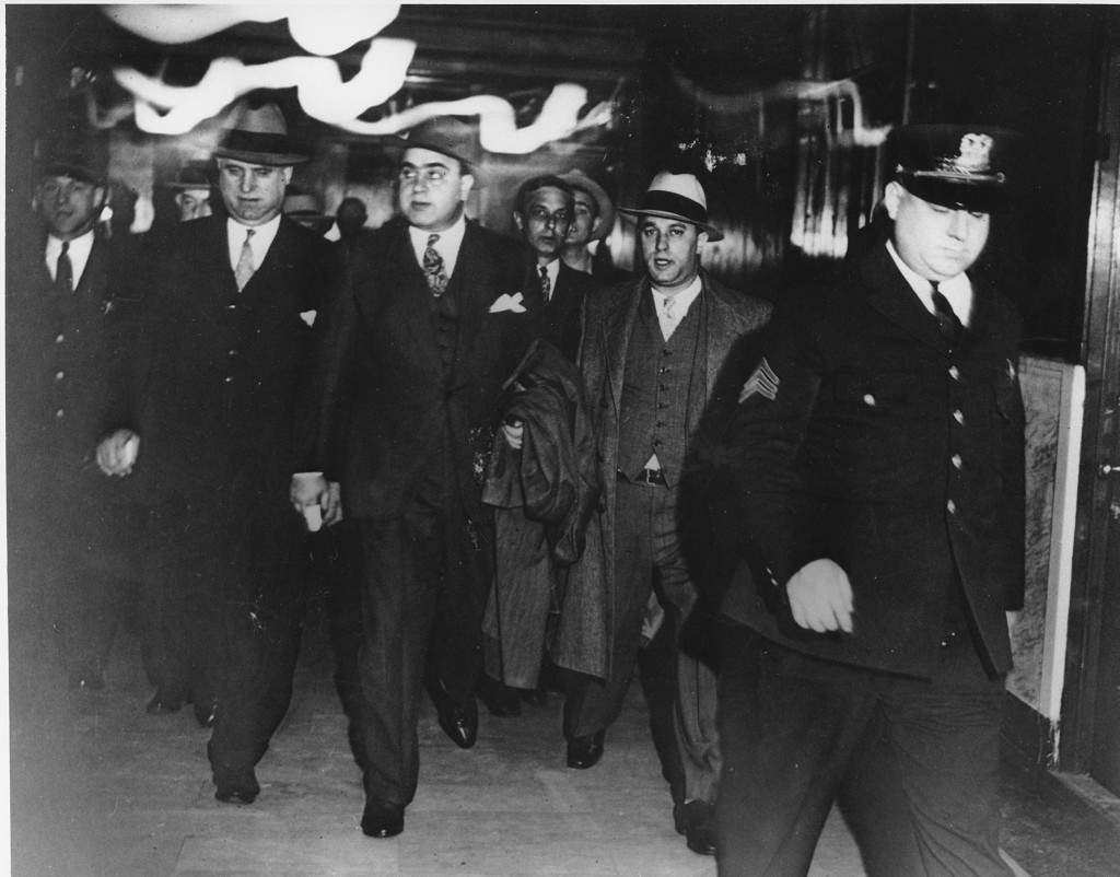 Chicago crime boss Al Capone, center, in the custody of U.S. marshals, leaves the courtroom of Federal Judge James H. Wilkerson in Chicago. Oct. 24th, 1931. He is facing tax evasion charges. Ref #: PA.2534968  Date: 24/10/1931