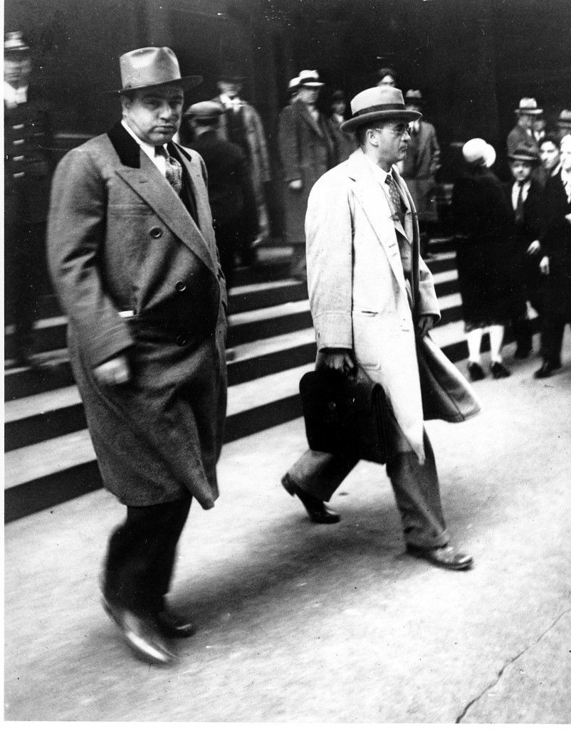 Al Capone looks at the camera as he walks out of Federal Court in Chicago with his attorney Michael Ahern. Oct. 11th, 1931. Capone is on trial for tax evasion Ref #: PA.2534974  Date: 11/10/1931