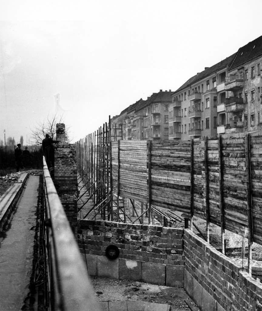 This is a view of the red brick wall on the border between East and West Berlin in Germany. The Communists have added a wooden fence to impede a clear view into the Communist East Berlin zone. At left, West Berlin police armed with automatic weapons patrol along the wall. PA-2637664