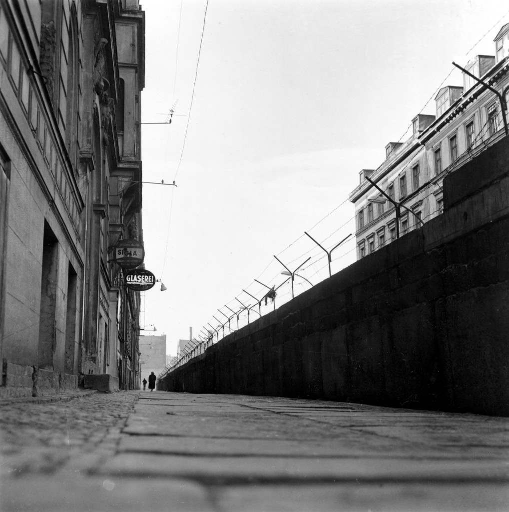 A high wall of concrete blocks, topped with barbed wire, divides Sebastian Strasse in the Kreuzberg district of Berlin, Germany. To the left is the American sector and beyond the wall to the right is the Russian sector. PA-2637686