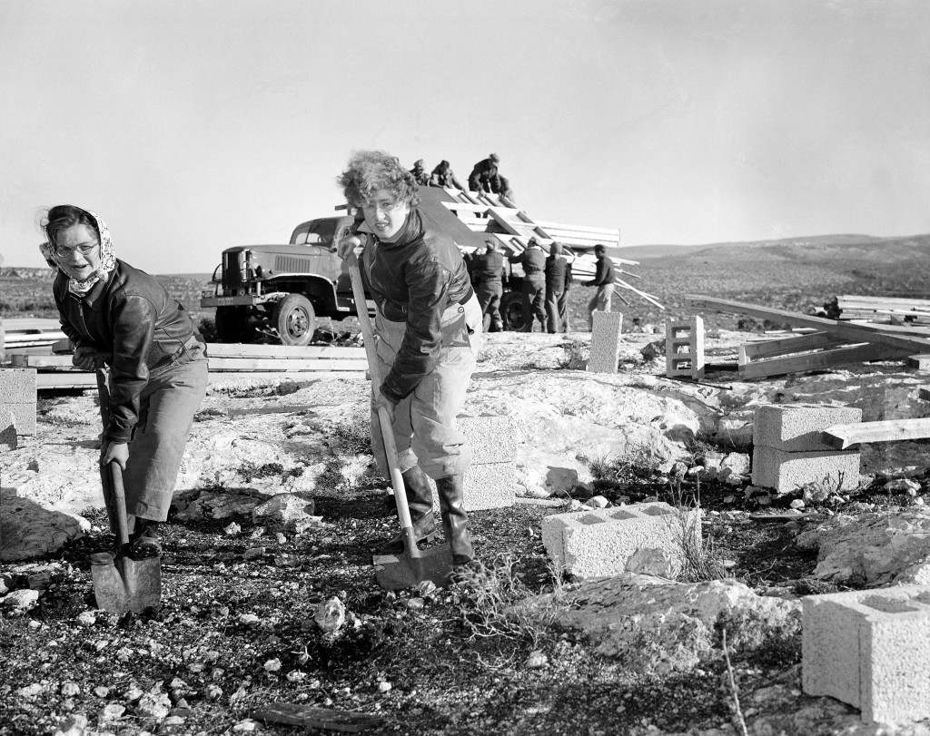 Miriam Wiess, left, of Glasgow, Scotland, and Leah Cohen, of Leeds, help clear ground for the erection of a building at the site of the new Israeli kibbutz settlement in Yazur, in western Galilee, Israel, Feb. 13, 1949. (AP Photo) Ref #: PA.2823960 Date: 13/02/1949