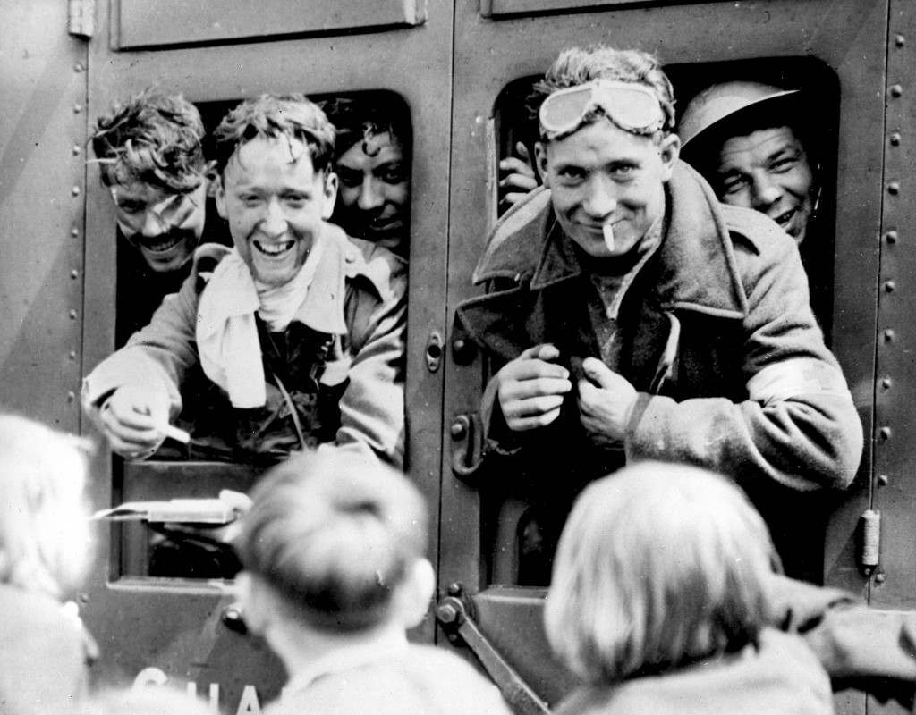 Returning soldiers of the B.E.F., British Expeditionary Force, smile through a train window en route to their home station in England on June, 1940. The one at left hands out a cigarette. (AP Photo) Ref #: PA.2842160  Date: 00/06/1940