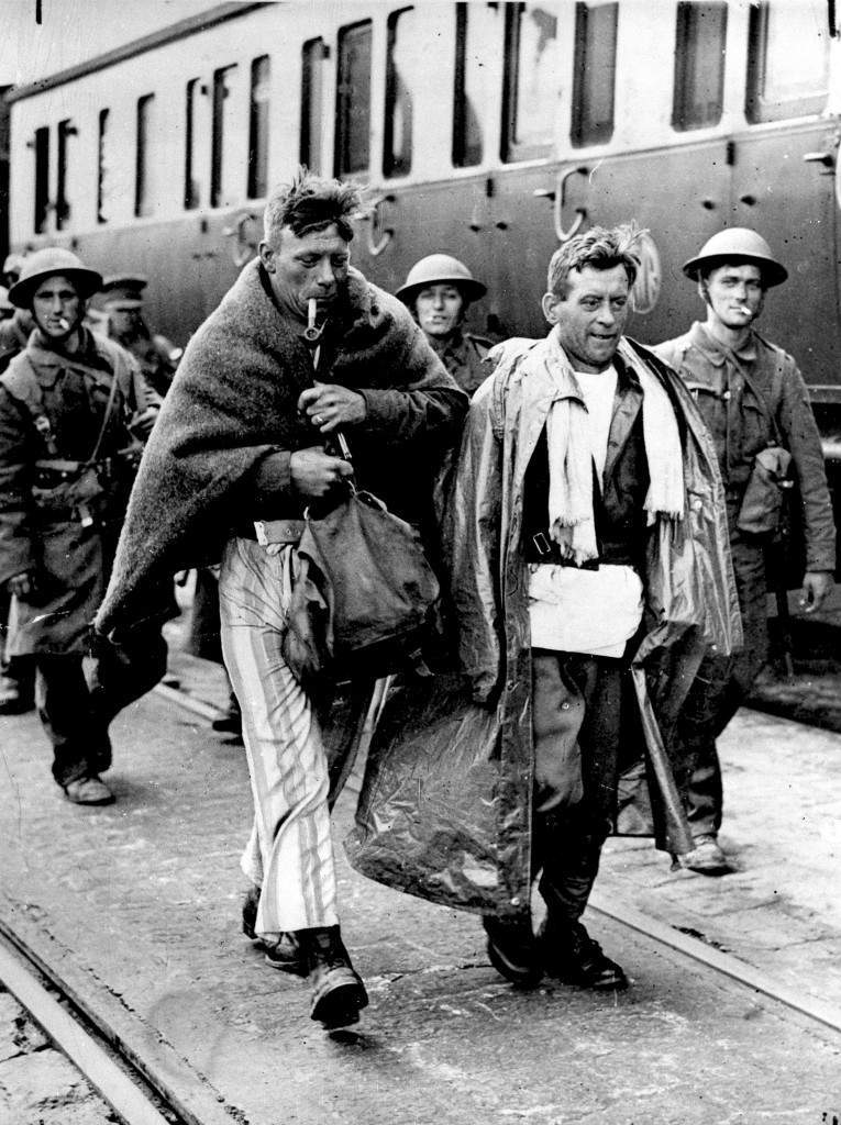 A group of British soldiers arrive in England after the evacuation of Flanders, France, on June 6, 1940 in World War II. The British soldier at left wears his pajamas instead of his uniform and a blanket around his shoulders for warmth and smokes a pipe. In Operation Dynamo, over three-hundred thousand French, British and Belgian troops escaped the German invasion from the beaches near Dunkirk, France. (AP Photo) Ref #: PA.2842177  Date: 06/06/1940