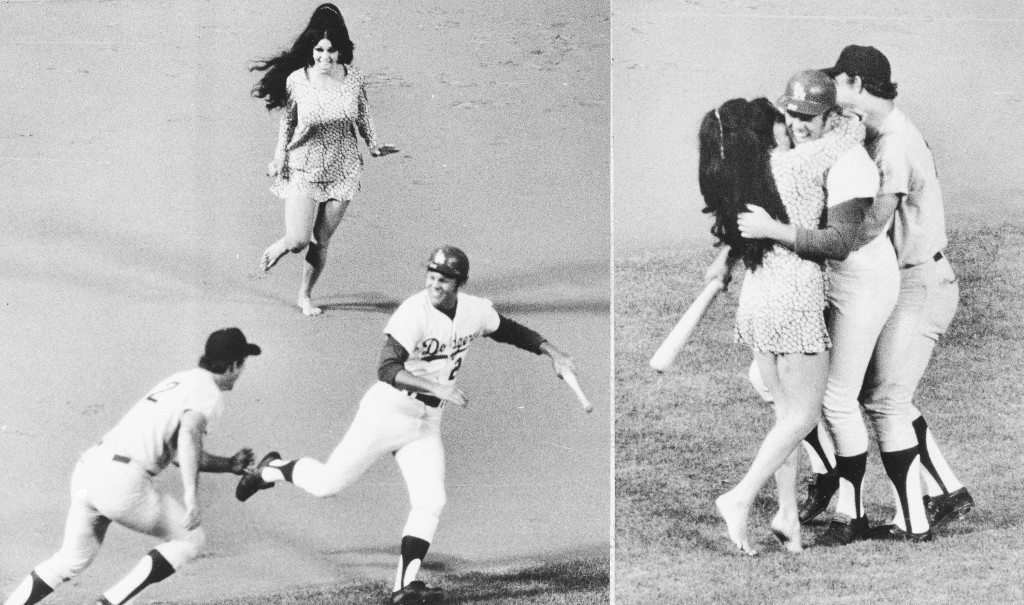 Morganna Roberts comes running out the stands to kiss Los Angeles Dodgers Wes Parker, who is being caught and held by Houston Astros third baseman Doug Rader (2) on Tuesday July 1, 1970 in Los Angeles, Calif. (AP Photo) Ref #: PA.2886194  Date: 01/07/1970