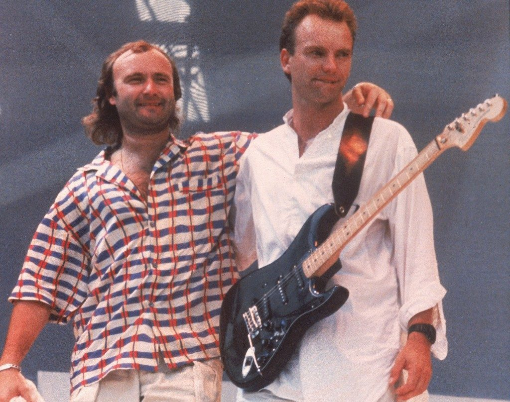 British pop singers Phil Collins, left, and Sting are shown on stage during the Live Aid concert held at London's Wembley Stadium, England, July 13, 1985. Collins will fly on the Concorde to perform at the Live Aid concert in Philadelphia, USA. The rock and roll telethon concert, to raise awareness for famine victims in Ethiopia, was broadcast around the world and raised $100 million dollars. (AP Photo/Joe Schaber)   PA-2964368