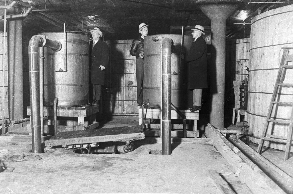 The largest distillery ever uncovered in Detroit was raided and prohibition officers are seen inspecting tanks and vats in one part of the plant, on Jan. 5, 1931. Each of these vats have a capacity of 15,000 gallons and there were thirteen on this floor alone. (AP Photo) Ref #: PA.3325793  Date: 05/01/1931