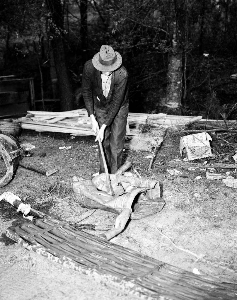 A U.S. federal agent uses an axe to destroy the copper equipment used in this large illegal liquor plant during a raid near Griffin, Ga., on May 5, 1937. (AP Photo) Ref #: PA.3388995  Date: 05/05/1937