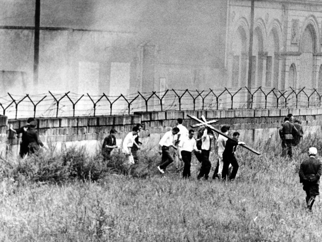 "West Berlin youths carrying a black cross with the slogan ""We Accuse"" are driven back from the sector border wall by tear gas from grenades fired by East German border guards near Wilhelmstrasse, Berlin, on Aug. 13, 1962. The protest marks the first anniversary of the Berlin Wall. (AP Photo) PA-3389216"