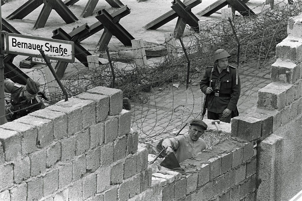 Backed up by barbed wire and tank barriers, an East German police officer stands guard while a bricklayer repairs damage to the Berlin Wall near Bernauer Strasse, May 26, 1962. The wall was damaged by several explosions overnight. (AP Photo/Werner Kreusch) PA-3389263