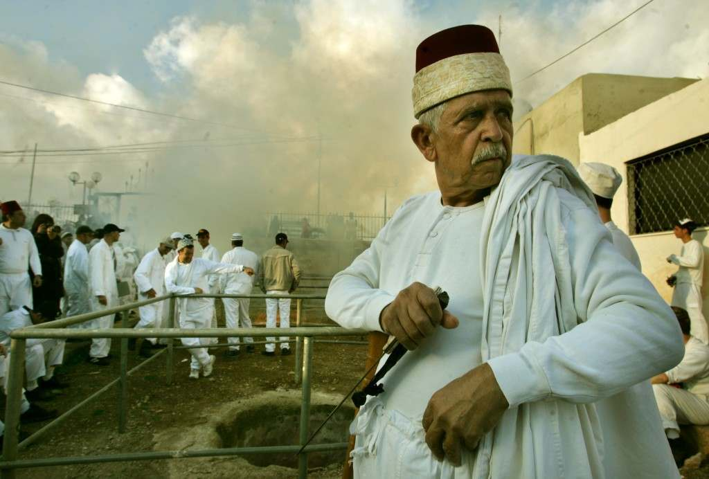 A Samaritan priest holds a knife before slaughtering sheep during the ritual of Sacrifice, part of a Samaritan Passover ceremony, in Mount Grizin, overlooking the West Bank town of Nablus, Tuesday April 11, 2006. Samaritans descended from the ancient Israelite tribes of Menashe and Efraim but broke away from mainstream Judaism 2,800 years ago. Today, the remaining 700 Samaritans, live in the Palestinian city of Nablus in the West Bank and the Israeli seaside town of Holon, south of Tel Aviv.(AP Photo/Baz Ratner) Ref #: PA.3410498  Date: 12/04/2006