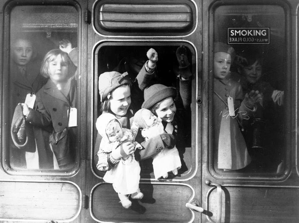 Two small girls hold their dolls while waving goodbye to relatives as they are evacuated to the west country, at a London station to escape the Nazi bombing, June 13, 1940. All the children wear identity labels. (AP Photo) Ref #: PA.3496537  Date: 13/06/1940