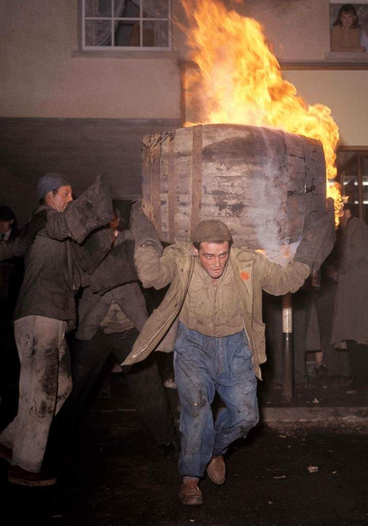 A file photo dated 05/11/1963 shows a man carrying a burning barrel on his shoulders as bystanders look on during a Tar Barrel Burning Ceremony in Ottery St Mary, Devon. PA-4013439