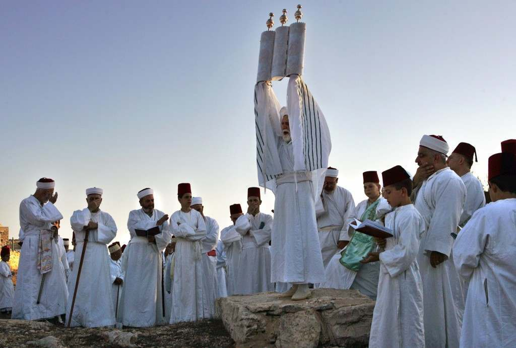A Priest of the ancient Samaritan community, wrapped in a prayer shawl, holds up a Tora scroll as worshippers pray during the pilgrimage for the holy day of the Tabernacles or Sukkot at the religion's holiest site on the top of Mount Gerizim near the West Bank town of Nablus, early Friday, Oct. 6, 2006. According to tradition, the Samaritans are descendants of Jews who were not deported when the Assyrians conquered Israel in the 8th century B.C. Of the small community of close to 700 people, half live in a village at Mount Gerizim, and the rest in the city of Holon near Tel Aviv. (AP Photo/Kevin Frayer) Ref #: PA.4032853  Date: 06/10/2006