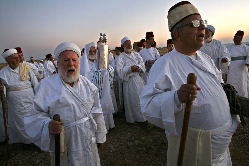 A Priest of the ancient Samaritan community, wrapped in a prayer shawl, carries a Tora scroll as worshippers walk during the pilgrimage for the holy day of the Tabernacles or Sukkot at the religion's holiest site on the top of Mount Gerizim near the West Bank town of Nablus, early Friday, Oct. 6, 2006. According to tradition, the Samaritans are descendants of Jews who were not deported when the Assyrians conquered Israel in the 8th century B.C. Of the small community of close to 700 people, half live in a village at Mount Gerizim, and the rest in the city of Holon near Tel Aviv. (AP Photo/Kevin Frayer) Ref #: PA.4032854  Date: 06/10/2006
