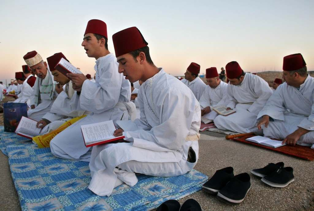 Members of the ancient Samaritan community read from their religious books as they pray during the pilgrimage for the holy day of the Tabernacles or Sukkot at the religion's holiest site on the top of Mount Gerizim near the West Bank town of Nablus, Friday, Oct. 6, 2006. According to tradition, the Samaritans are descendants of Jews who were not deported when the Assyrians conquered Israel in the 8th century B.C. Of the small community of close to 700 people, half live in a village at Mount Gerizim, and the rest in the city of Holon near Tel Aviv. (AP Photo/Kevin Frayer) Ref #: PA.4032870  Date: 06/10/2006