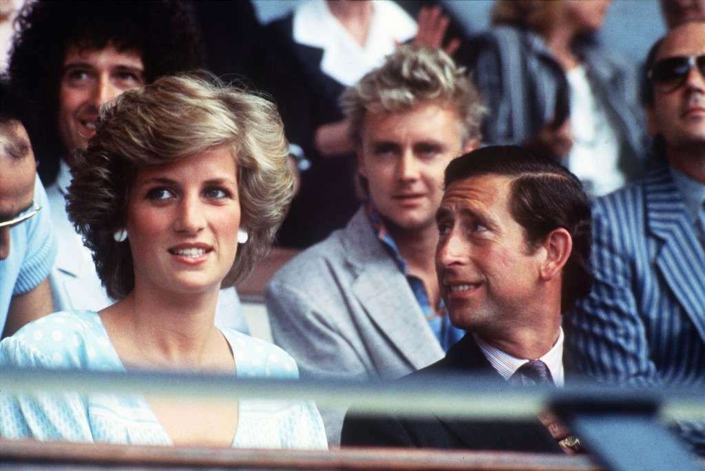 Britain's Prince Charles and Princess Diana watch Live Aid, a concert organised to raise money for famine relief in Africa, at Wembley Stadium, London, July 13, 1985. Seated behind are Brian May, left, and Roger Taylor, right, of British rock band Queen. (AP Photo) PA-1880417