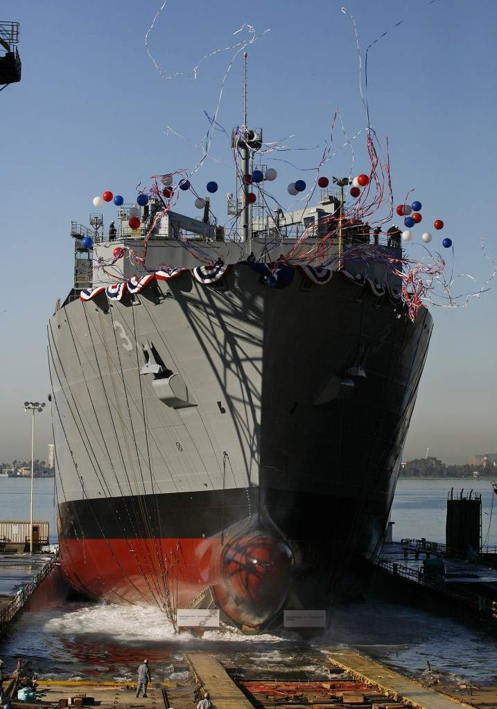 Workmen look on as the USNS Alan Shepard slides into the water as the ship is launched at the General Dynamics NASSCO shipyard Wednesday, Dec. 6, 2006 in San Diego. The USNS Alan Shepard, named in honor of the NASA astronaut, is the third ship of an expected class of 11 T-AKE dry cargo-ammunition ships to be built by General Dynamics NASSCO for the U.S. Navy. (AP Photo/Denis Poroy) Ref #: PA.4208336