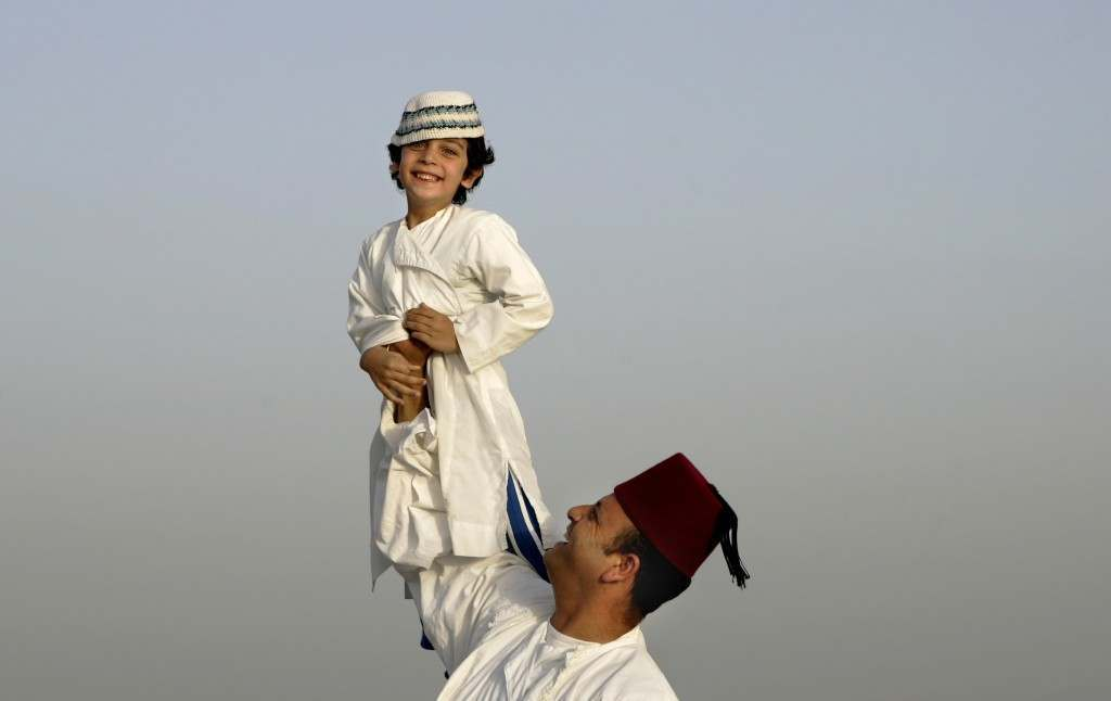 A father from the Ancient Samaritan community holds up his son during a pilgrimage marking the end of the holy day of Passover at the religion's holiest site on Mount Gerizim near the West Bank town of Nablus, early Monday, May 7, 2007. According to tradition, the Samaritans are descendants of Jews who were not deported when the Assyrians conquered the area in the 8th century B.C. Of the small community of close to 700 people, half live in a village at Mount Gerizim, and the rest in the city of Holon near Tel Aviv. (AP PhotoAriel Schalit) Ref #: PA.4631675  Date: 07/05/2007