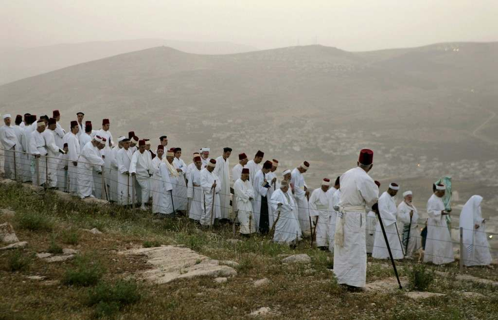 Members of the Ancient Samaritan community walk during a pilgrimage marking the end of the holy day of Passover at the religion's holiest site on Mount Gerizim near the West Bank town of Nablus, early Monday, May 7, 2007. According to tradition, the Samaritans are descendants of Jews who were not deported when the Assyrians conquered the area in the 8th century B.C. Of the small community of close to 700 people, half live in a village at Mount Gerizim, and the rest in the city of Holon near Tel Aviv. (AP Photo/Ariel Schalit) Ref #: PA.4631688  Date: 07/05/2007