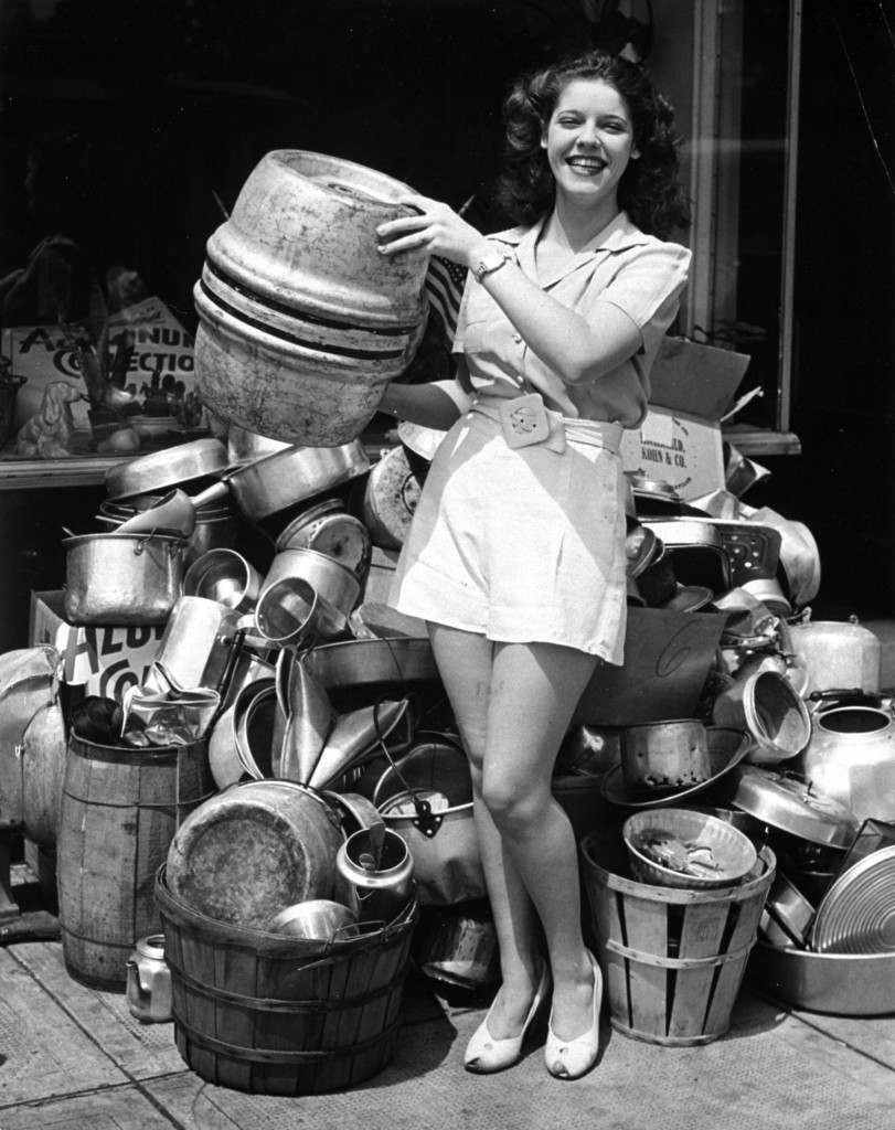 "Marie Beiser, Baltimore beauty, took a personal hand in collecting scrap aluminum for defense purposes, July 25, 1941. Among the articles she added to a pile of castoffs gathered by her mother was an old aluminum beer keg of the pre-prohibition era. Marie was ""Miss Maryland"" in the 1940 Atlantic City beauty pageant. (AP Photo) Ref #: PA.4716172  Date: 25/07/1941"