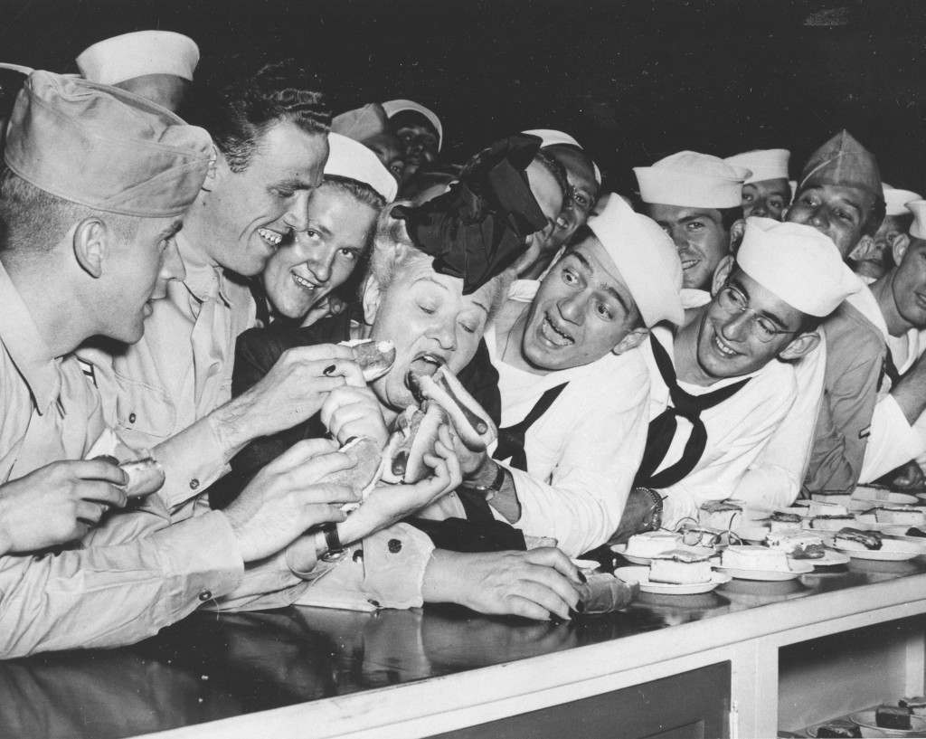 Sailors joke with radio personality Sophie Tucker and feed her multiple hot dogs at the United Service Organizations (USO) center in Chicago, Ill., July 2, 1944. From left are, Marine Pvt. Art McCarroll, of Pittsburgh, Pa.; Corp. Verne Hink, of Oklahoma City, Okla.; Seaman Fred Bishara, Binghamton, N.Y.; and Seaman Alan Frank, Salt Lake City, Utah. (AP Photo) Ref #: PA.4760360