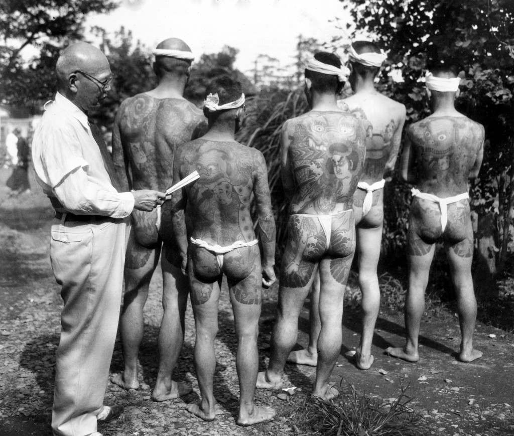 Japanese tattoo artist Ginjiro Susuki, 72, left, exhibits some of his tattoo designs at the Hard Skin Club convention of tattooed men and women held in Tokyo, Japan, Sept. 2, 1948. Suzuki estimates that he has tattooed more than 10,000 persons in his lifetime devotion to the 300-year-old art. (AP Photo) Ref #: PA.4770680
