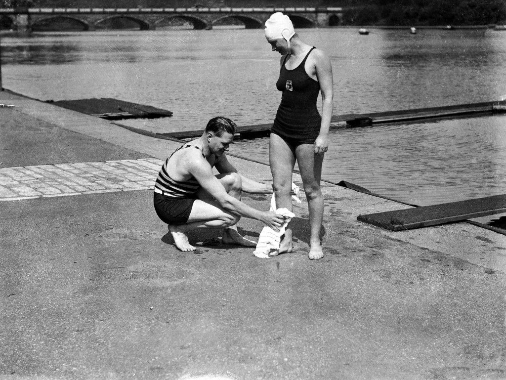 Miss Eva Coleman, who intends to attempt the Channel swim this summer, is using the Hyde Park Lido as a training ground. Her trainer, Burgess, considers she has a good chance of breaking the record set up by Gertrude Ederle. Picture shows Miss Eva Coleman receiving a towelling down from her trainer, Burgess, after her swim Ref #: PA.477625  Date: 19/05/1932