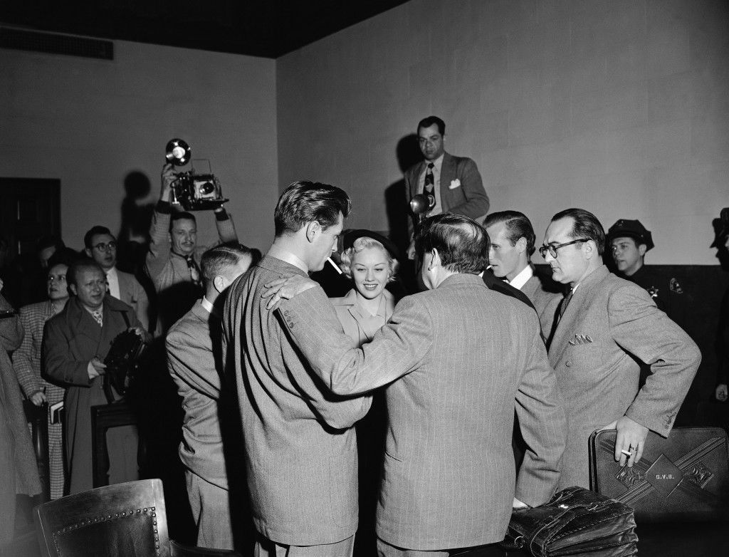 Robert Mitchum and Lila Leeds, both at left, talk with their attorneys and real estate man Robin Ford, second from right, immediately after the screen players and Ford were convicted, Jan 10, 1949 in Los Angeles. They were convicted of conspiracy to possess marijuana. Jerry Gieser, Mitchum's attorney, has his back to the camera. At right is V. G Brumdaugh, Ford's Attorney. Trial on the other count in their indictments, possession of narcrotics, was postponed. (AP Photo) Ref #: PA.4949502