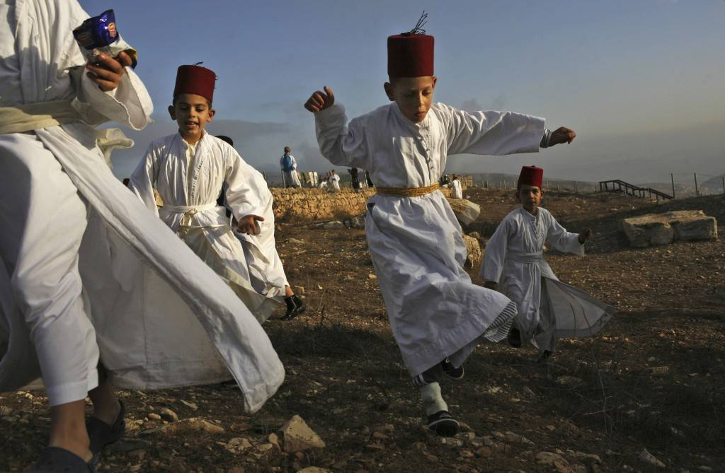 Samaritan children play during the pilgrimage for the holy day of the Tabernacles or Sukkot at the religion's holiest site on the top of Mount Gerizim near the West Bank town of Nablus, early Thursday Oct. 25,2007. According to tradition, the Samaritans are descendants of Jews who were not deported when the Assyrians conquered Israel in the 8th century B.C. Of the small community of close to 700 people, half live in a village at Mount Gerizim, and the rest in the city of Holon near Tel Aviv. (AP Photo/Kevin Frayer) Ref #: PA.5278409  Date: 25/10/2007