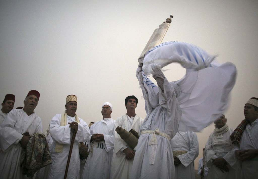 A priest of the ancient Samaritan community, wrapped in a prayer shawl, holds up a Tora scroll as worshippers pray during the pilgrimage for the holy day of the Tabernacles or Sukkot at the religion's holiest site on the top of Mount Gerizim near the West Bank town of Nablus, early Thursday Oct. 25,2007. According to tradition, the Samaritans are descendants of Jews who were not deported when the Assyrians conquered Israel in the 8th century B.C. Of the small community of close to 700 people, half live in a village at Mount Gerizim, and the rest in the city of Holon near Tel Aviv. (AP Photo/Kevin Frayer) Ref #: PA.5278417  Date: 25/10/2007