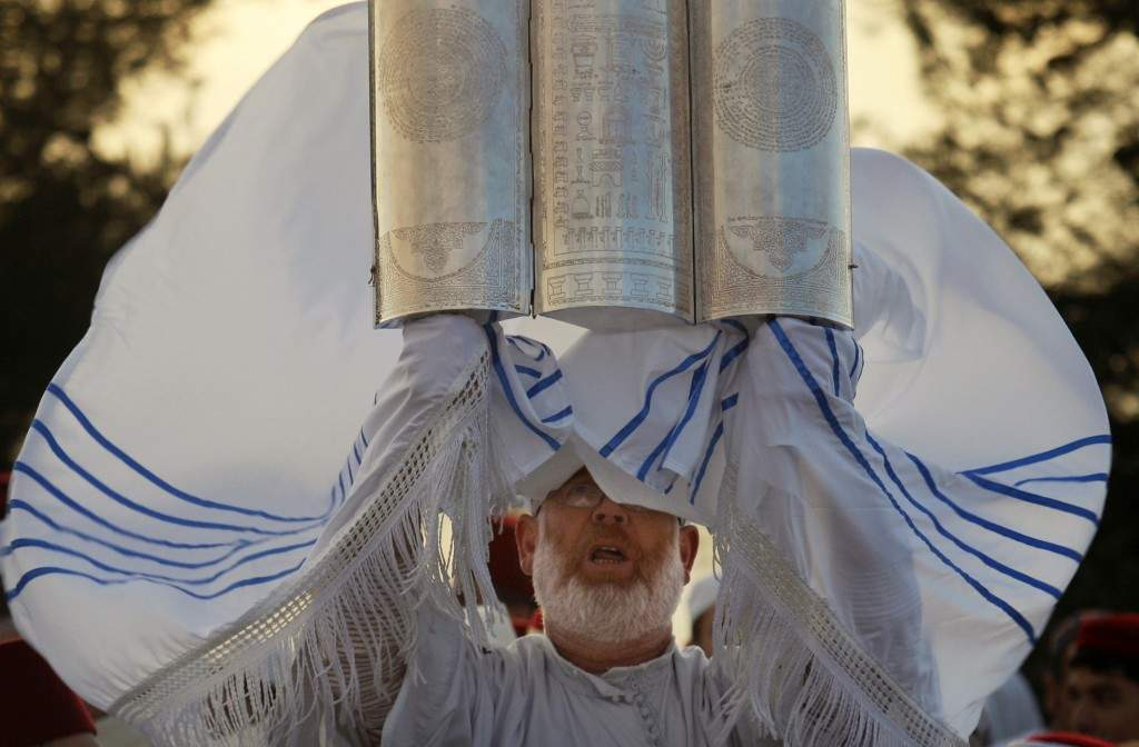 A Priest of the ancient Samaritan community, wrapped in a prayer shawl, holds up a Tora scroll during the pilgrimage for the holy day of the Tabernacles or Sukkot at the religion's holiest site on the top of Mount Gerizim near the West Bank town of Nablus, early Thursday Oct. 25,2007. According to tradition, the Samaritans are descendants of Jews who were not deported when the Assyrians conquered Israel in the 8th century B.C. Of the small community of close to 700 people, half live in a village at Mount Gerizim, and the rest in the city of Holon near Tel Aviv. (AP Photo/Kevin Frayer) Ref #: PA.5278431  Date: 25/10/2007