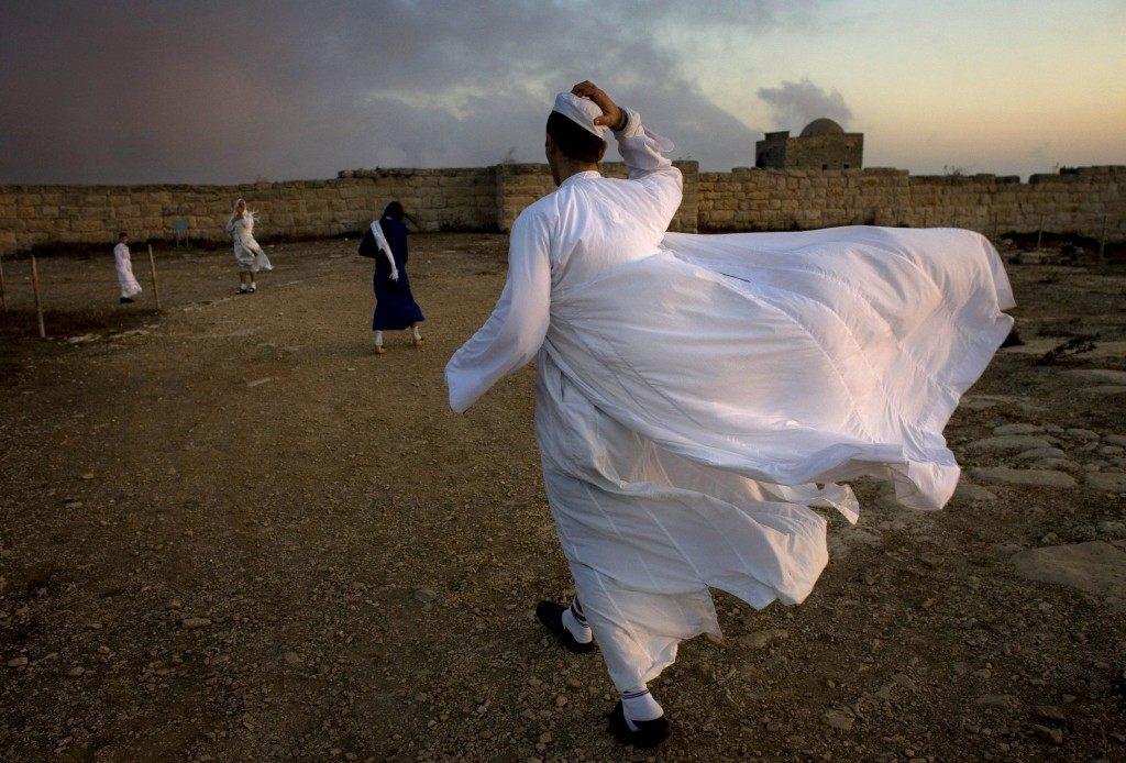 A priest of the ancient Samaritan community walks during the pilgrimage for the holy day of the Tabernacles or Sukkot at the religion's holiest site on the top of Mount Gerizim near the West Bank town of Nablus. Picture date: Thursday Oct. 25, 2007. According to tradition, the Samaritans are descendants of Jews who were not deported when the Assyrians conquered Israel in the 8th century B.C. Of the small community of close to 700 people, half live in a village at Mount Gerizim, and the rest in the city of Holon near Tel Aviv. (AP Photo/Oded Balilty) Ref #: PA.5278445  Date: 25/10/2007