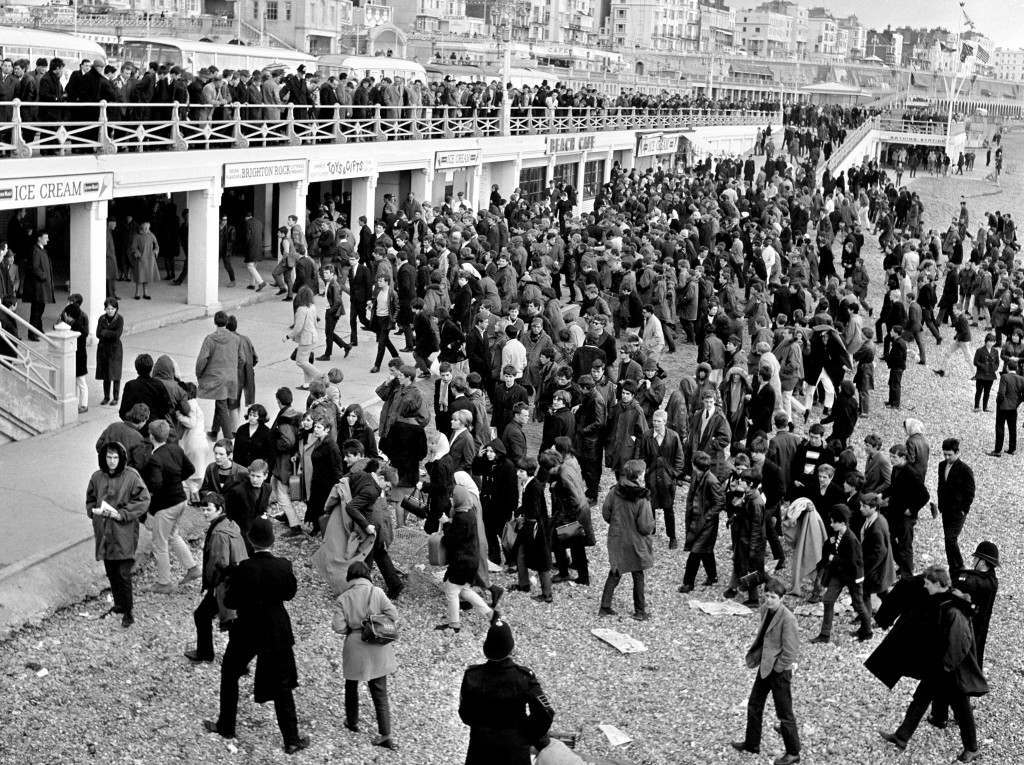 Interested onlookers watch from the promenade railings as police shepherd a large crowd of youths from the beach at Brighton on Bank Holiday Monday. Mass fights between Mods, Rockers and police erupted in seaside resorts throughout the summer of 1964, as intense rivalry between the motorcycle-based Rockers and the moped-riding Mods led to violence. Ref #: PA.5581335  Date: 19/04/1965