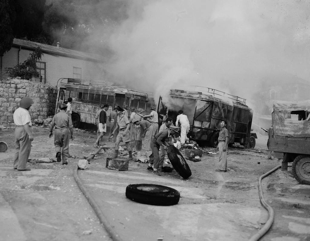 Jewish firefighters engage in salvage operations as smoke still rises from two buses set aflame when a parking lot along Jaffa Road in Jerusalem was struck by Arab incendiary mortar shells, June 12, 1948. The parking lot was hit during one of the daily shellings of the new section of the city by the Arab legion. (AP Photo/Tom Fitzsimmons) Ref #: PA.5736812 Date: 12/06/1948